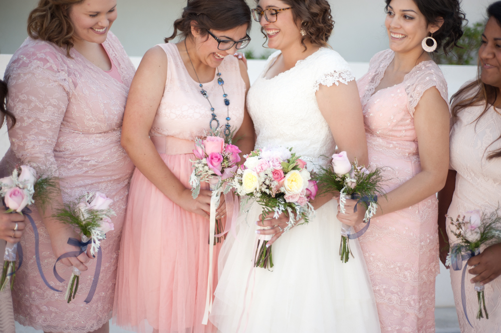 Bride and pink blush bridesmaids laughing