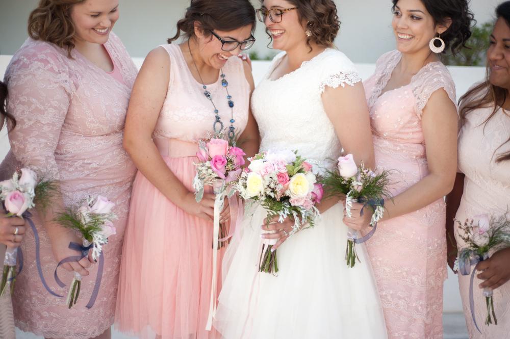 Bride and pink blush bridesmaids laughing