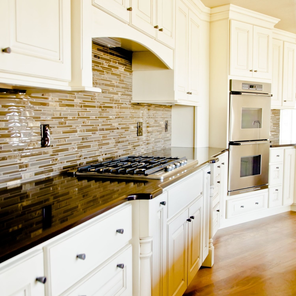 Open kitchen interior with glass tile backsplash and gas stove