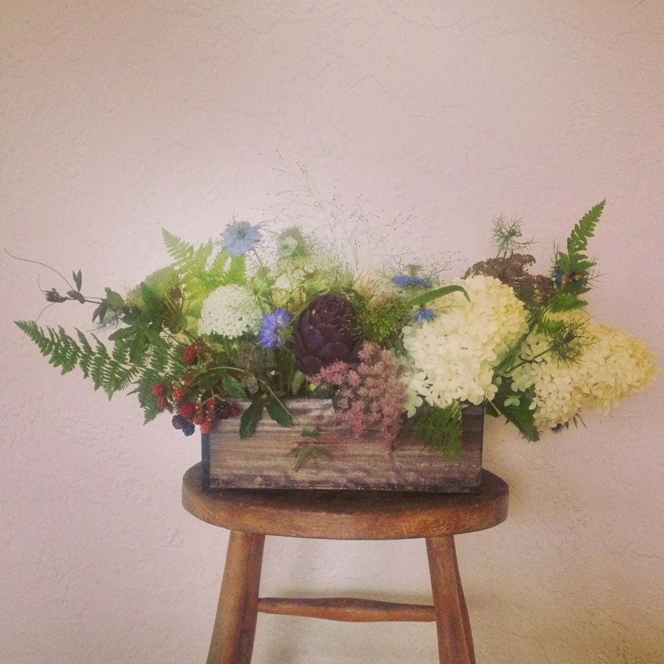 Centerpieces were design in reclaimed wood boxes and filled with seasonal flowers and berries and ferns from the woods.