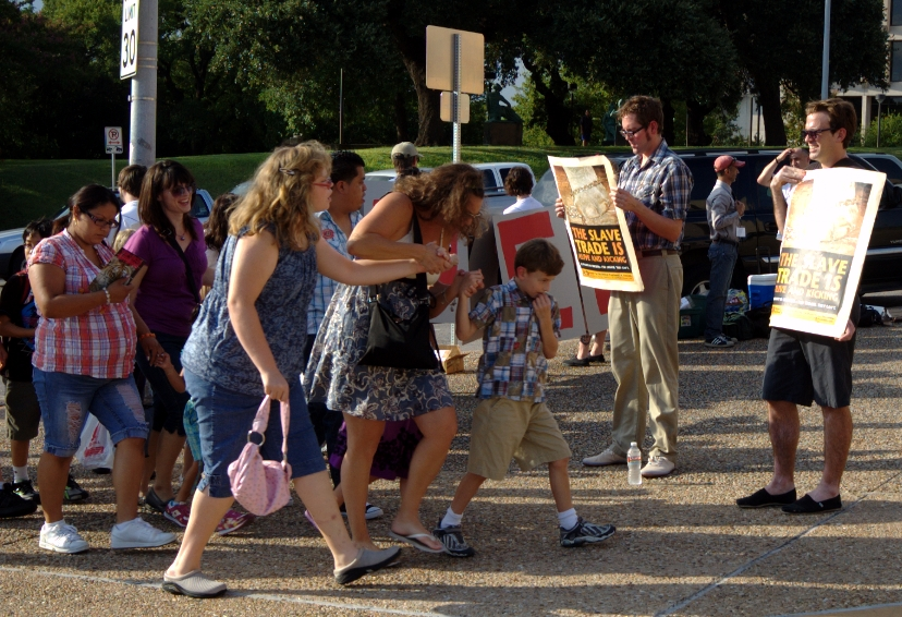 A family avoids protester's signs at the Barnum Circus during its stop in Austin, Texas
