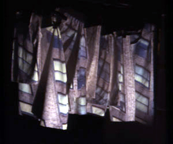 View from video installation, projection onto white clothing as screen; 2000. A three- generation collaboration with the artists' mom and grandmother, who sewed the clothes used as the projection screen.