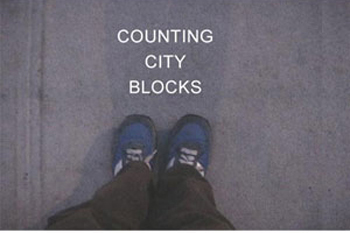 2003, video still, artist walked around on square block counting each foot step taken.