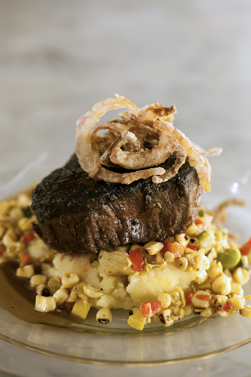 Blackened filet mignon with truffle mashed potatoes, charred corn and pepper succotash with bordelaise sauce