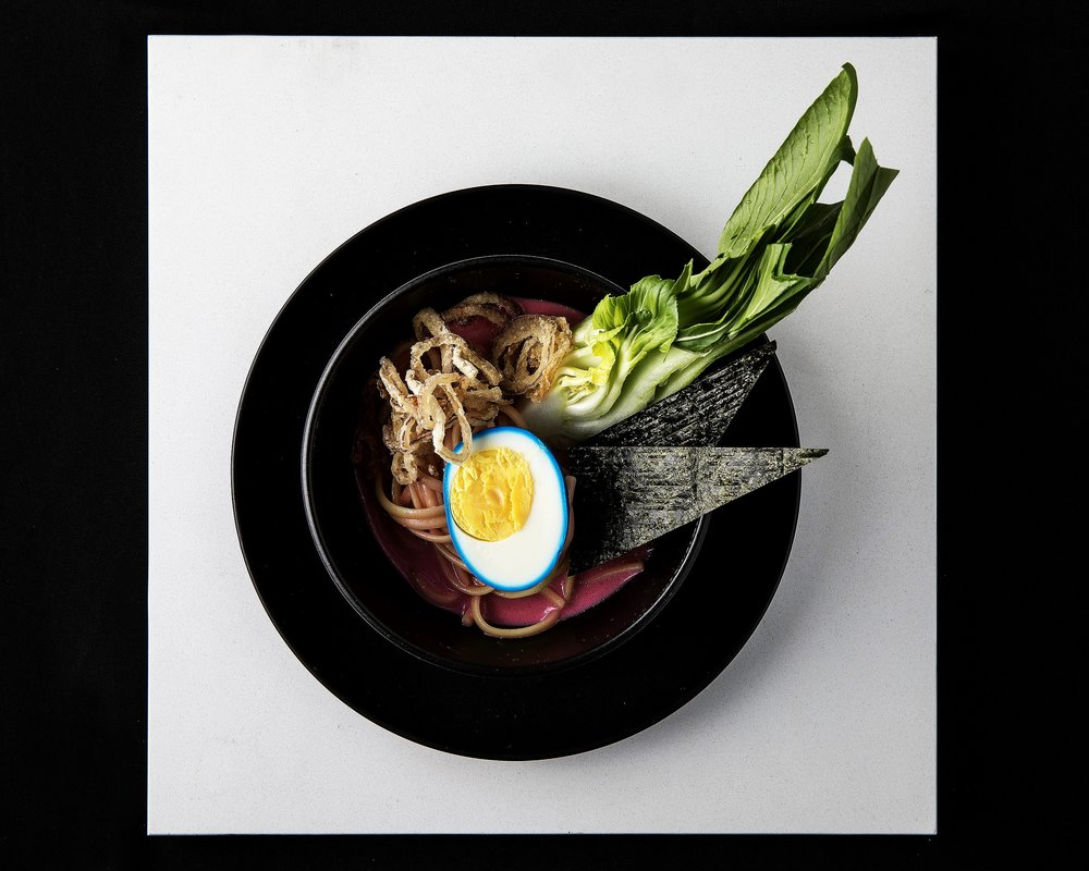 Ramen with pink broth, blue soft boiled egg and crispy onion