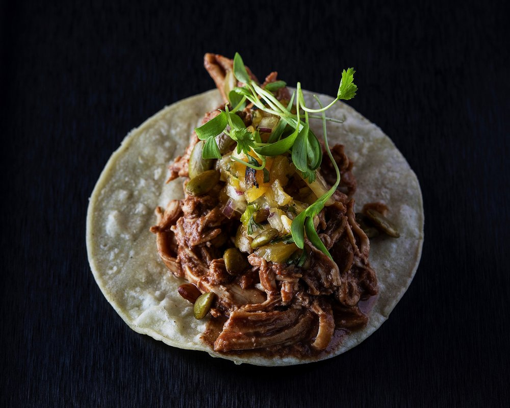Pulled pork taco with salsa verde, pepitas and micro greens