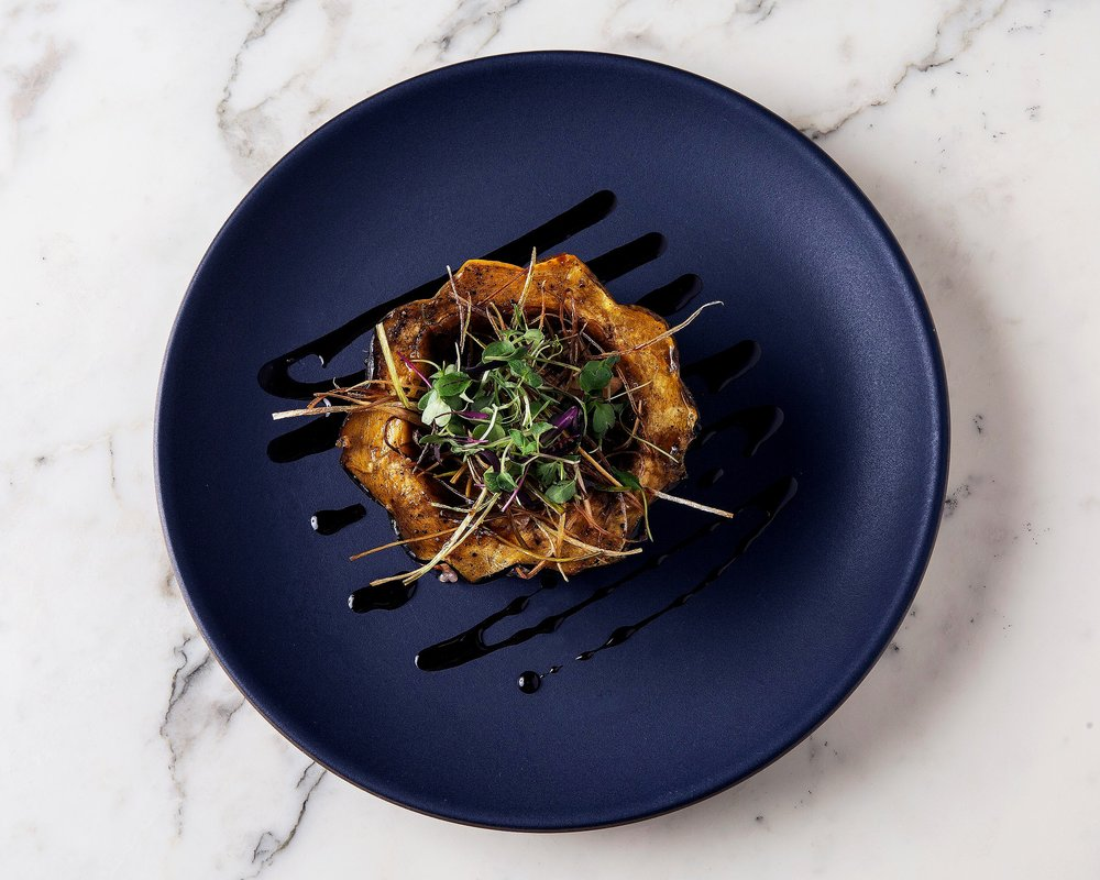 Stuffed acorn squash with rice and balsamic glaze with micro greens