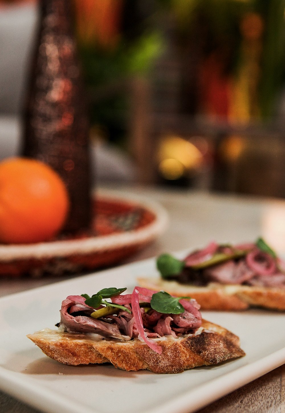 Crostini with slice beef and pickled red onion