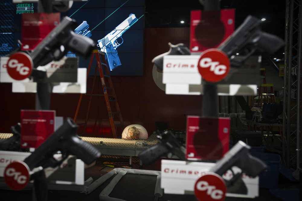 A worker helps set up the Crimson Trace booth at the 2013 National Rifle Association Meeting and Exhibits May 2, 2013 in Houston. Crimson Trace manufactures laser sights in both red and green.