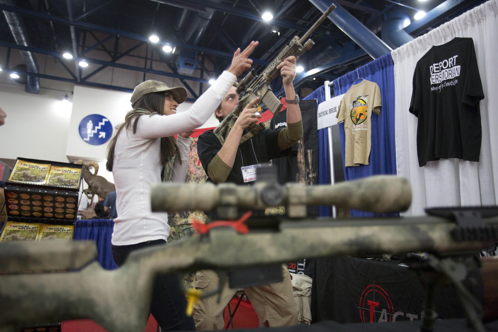 Vianne Euresti, left, and Jack Dougherty, of Tactical Rifles, looks down the sight of a M-4 at the 2013 National Rifle Association Meeting and Exhibits May 3, 2013 in Houston.