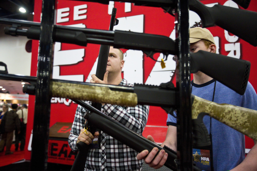 David Goodrum, left, and brother Matt, look at SAR semi automatic home defense 12 gauge shotguns at the 2013 National Rifle Association Meeting and Exhibits May 4, 2013 in Houston.