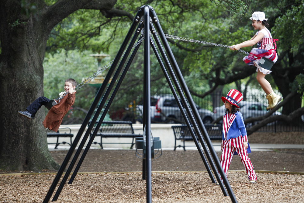 """Reece Tanig, 6, left, Bianca Bolanos, 10, and Kaylee Tanig, 9 — dressed as Benjamin Franklin, Uncle Sam and Betsy Ross — hit the swings Monday at Sam Houston Park after helping Mayor Annise Parker unveil plans for Houston's official Fourth of July celebration, Southwest Airlines Freedom Over Texas, which will include fireworks and a performance by Jennifer Nettles."""