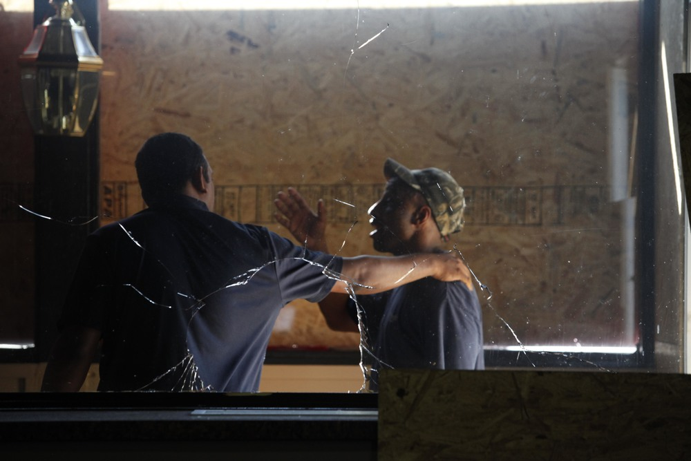 The owner of Red's Barbecue, left, speaks with a man making repairs to the restaurant.