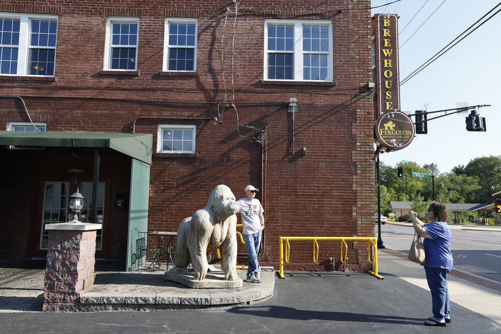 Linda Owen takes a photo of her husband Al August 19, 2014 in Ferguson, MO in front of the Ferguson Brewing Company. The couple are from an unincorporated section of St. Louis County and were visiting Ferguson to help support the town.