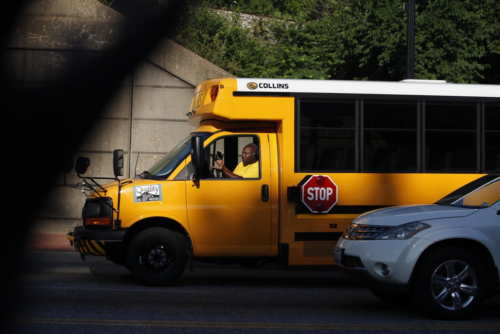A school bus driver gestures while waiting at a stoplight August 19, 2014 in downtown Ferguson, MO.