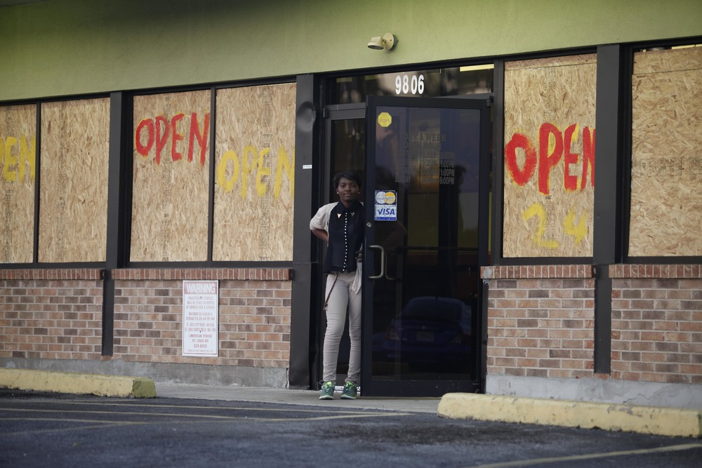 A woman stands before a chop suey restaurant August 19, 2014 in Ferguson, MO along W. Florissant Ave. where rioting took place earlier in the week.