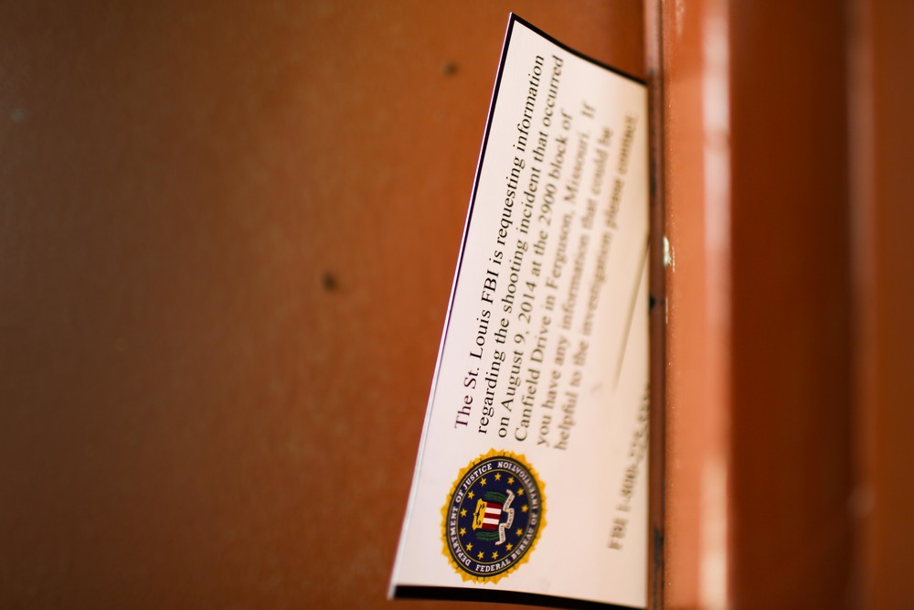 A card from the FBI stuck in the door in a third floor apartment overlooking the street where Michael Brown was shot and killed August 20, 2014 in Ferguson, MO. The apartment appeared to be empty and in disrepair as viewed through the undraped window.