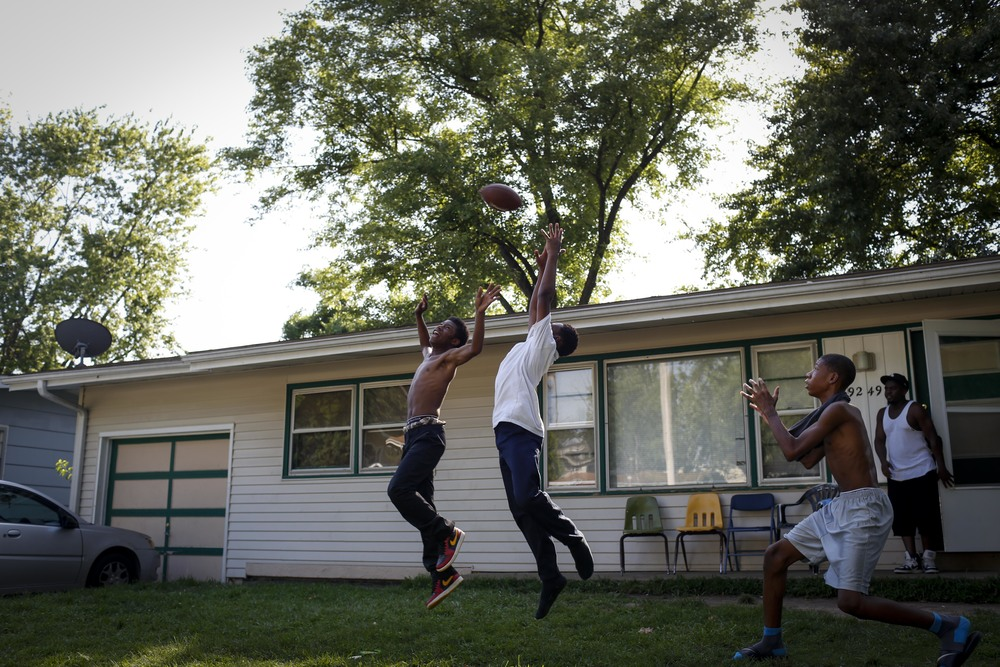 DeShawn White, 12, left, Tayron Wilhite, 13, and Ricky Allen, 15, toss a football around August 20, 2014 in Ferguson, MO. They were playing just around the corner from where Michael Brown was shot and killed by a Ferguson police officer.