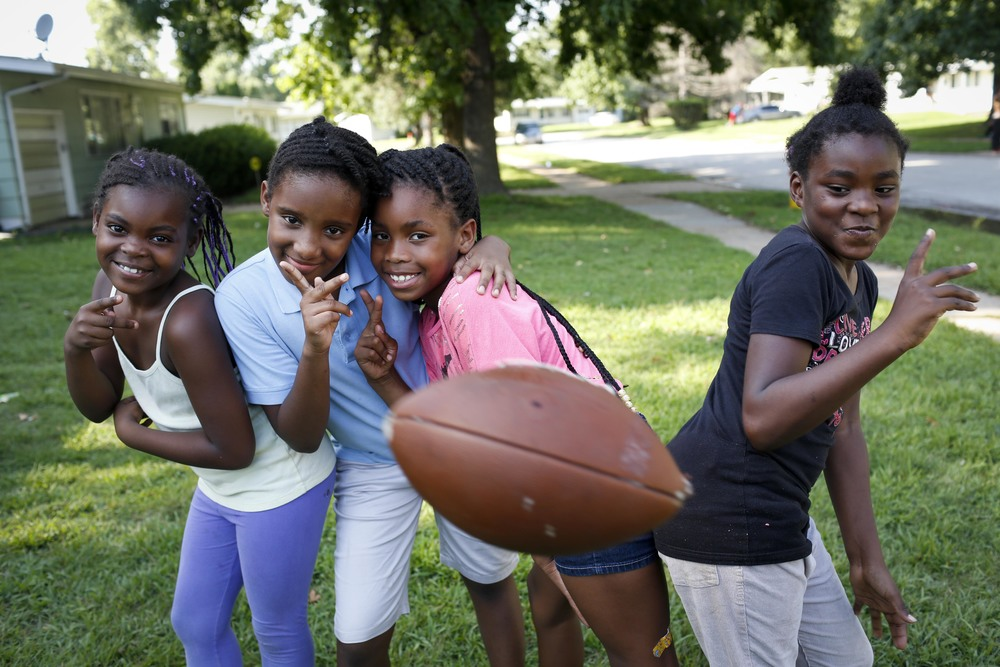 A football is tossed in front of Trice Johnson, 8, left, Jamyla Bolden, 8, Destiny Sonnier, 8, and Rayell Hickman, 8, as they pose for a photo August 20, 2014 in Ferguson, MO. The kids were in a yard  just around the corner from where Michael Brown was shot and killed by a Ferguson police officer.