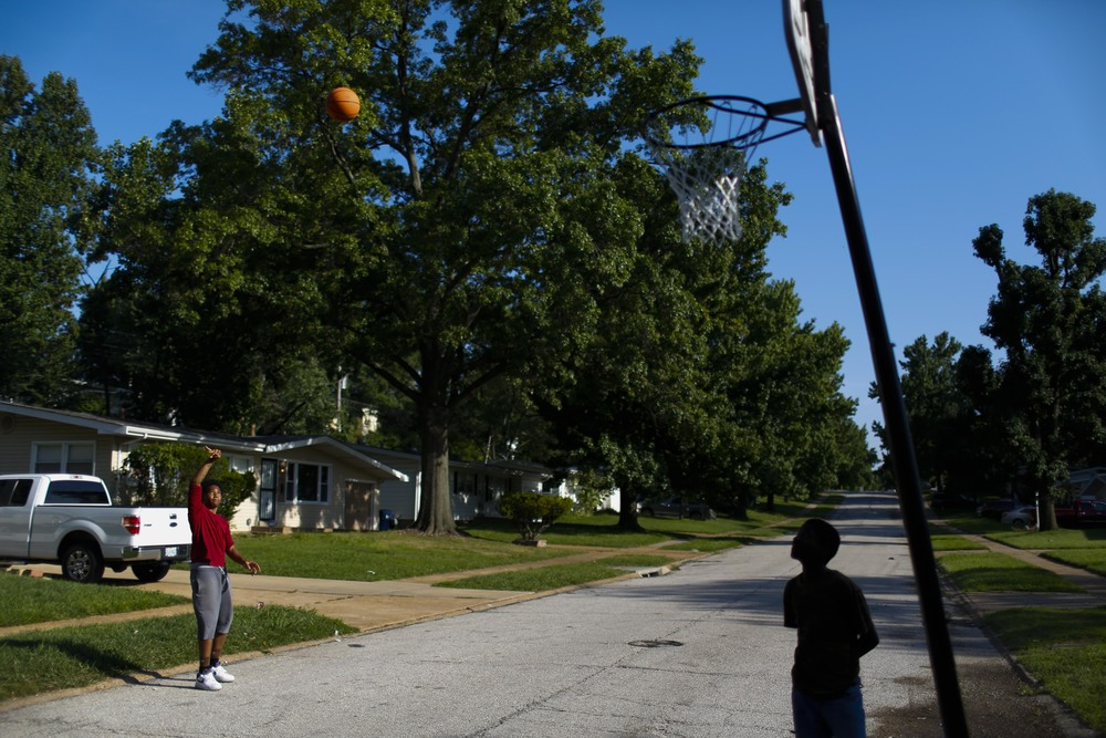 Two kids play basketball on Ellison Road, just around the corner from where Michael Brown was shot and killed by a Ferguson police officer. August 20, 2014 in Ferguson, MO.