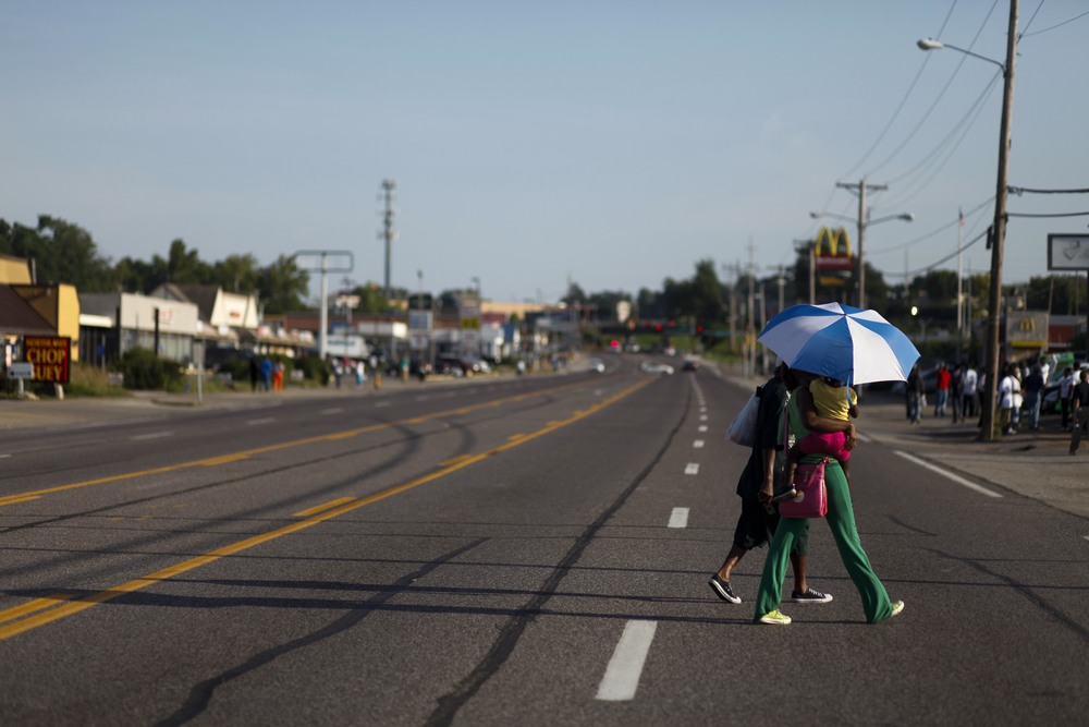 People cross W. Florissant Ave. as evening approaches August 20, 2014 in Ferguson, MO. The protest that evening was smaller and more calm than prior evenings.