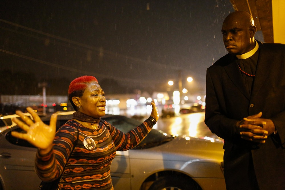 Elder Jason Watts, right, of the Williams Temple Church of God and Christ, listens to a woman who claimed she heard from God that the rain was a symbol that something bad was coming August 20, 2014 in Ferguson, MO.