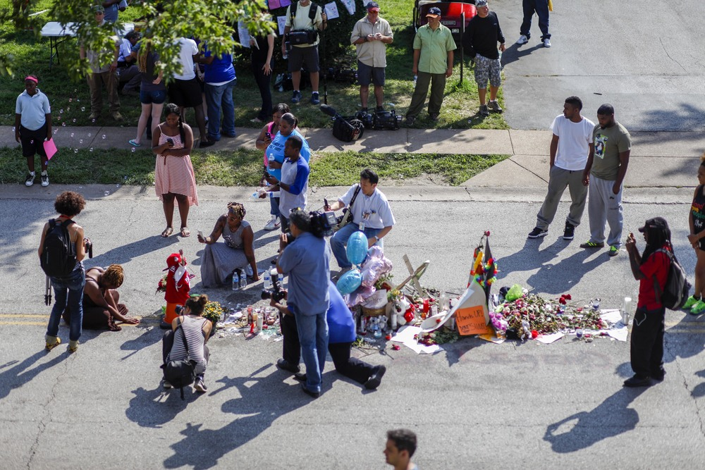A woman, left, sings at a memorial where Michael Brown was shot on August 9, 2014 on Canfield Drive. Photographed August 20, 2014 in Ferguson, MO.