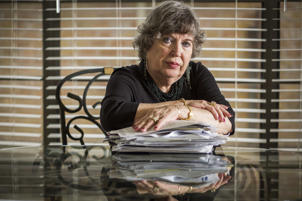 Barbara Beard by a stack of paperwork connected to her dispute with medical providers Feb. 5, 2014 in Katy, TX. Beard's husband was discharged from a long-term hospital after a 23 day stay to rehab following a botched knee surgery, and later died.