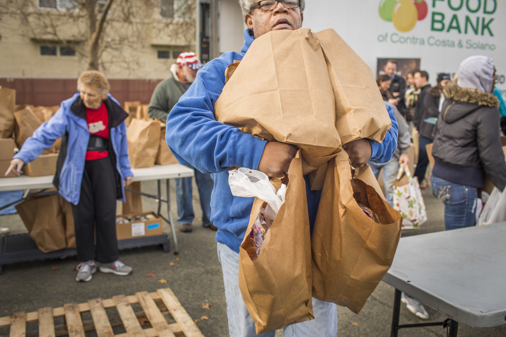 People receive donated groceries from the Contra Costa Food Bank, Tuesday, Dec. 13, 2016 in Rodeo, CA.