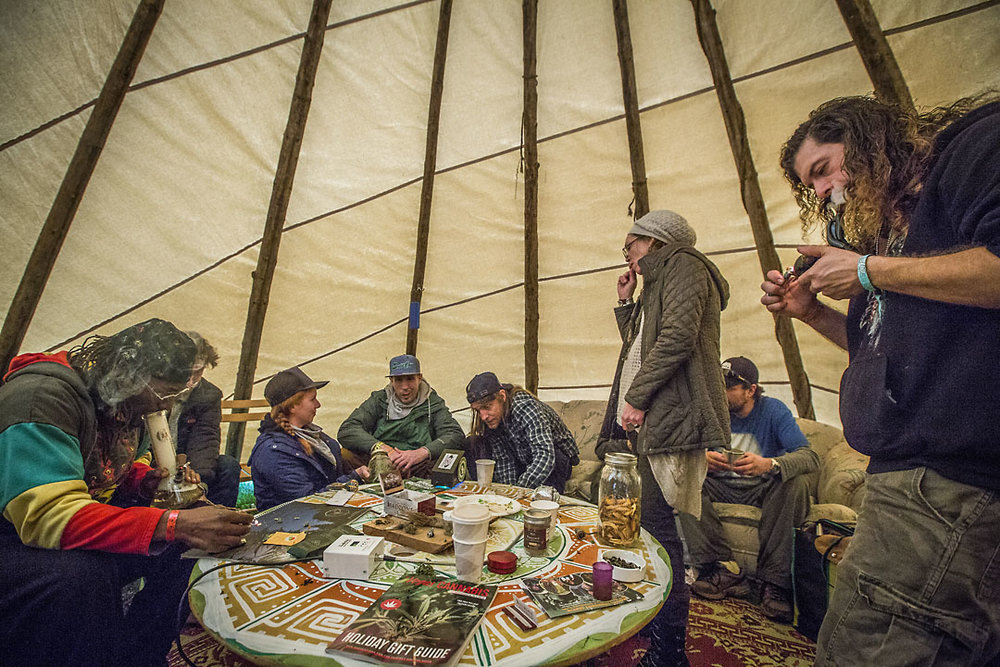 Friends gather inside a teepee to smoke and relax inside a teepee at the Emerald Cup.