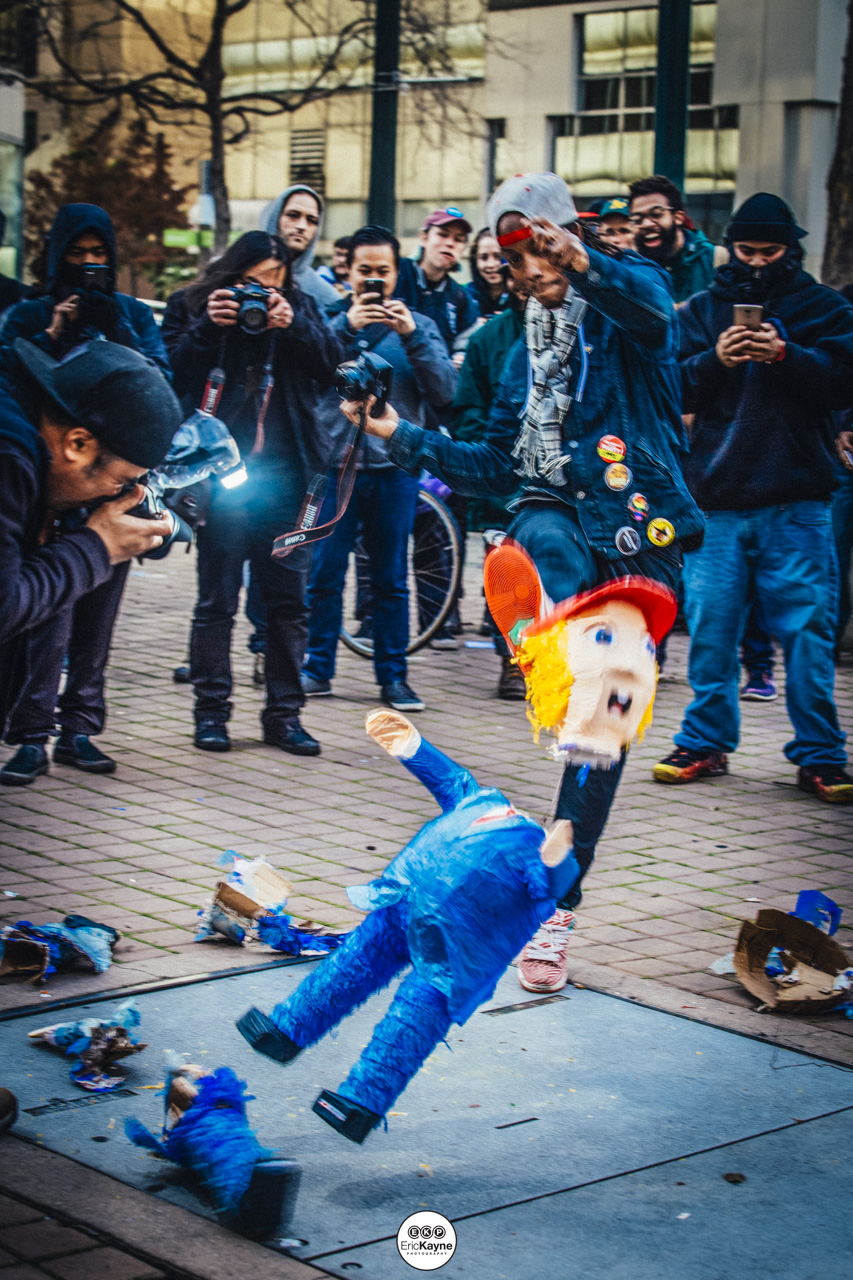 A protestor kicks a Donald Trump piñata at an anti-Trump rally marches into downtown Oakland, Friday, Jan. 20, 2017 in Oakland, CA.