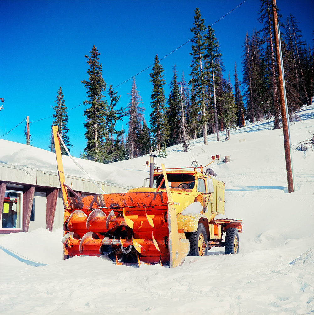 """A giant snow plow rests at Monarch Pass in Colorado. The pass sits on the continental divide at an elevation of 11,312 feet above sea level. I had great weather during the road trip and going through the pass in the middle of winter was a breeze – no snow plow required! Seeing this bright orange snow plow reminded me of a funny story my wife told me about learning to drive a stick-shift as a teenager. My mother-in-law told her she'd need to know how just in case she ever needed to drive a Snow-Cat. It seems hilarious because my wife is from St. Louis. But I suppose that since """"The Shining"""" was still relatively fresh in people's minds in those days, we all probably should have learned how to drive a Snow-Cat."""