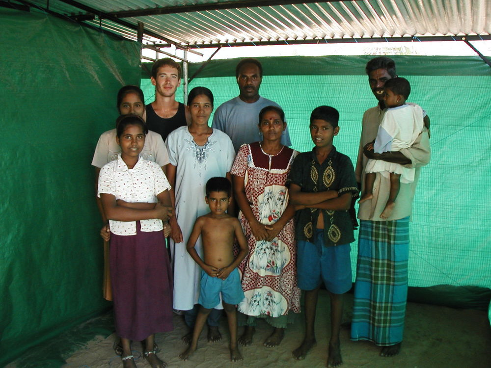 Jeremy and the crew with a family in their new temporary shelter.