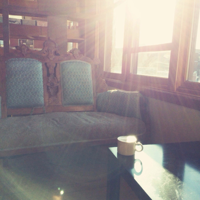 choosing the seat where the sun beams are draped over it with my coffee with breve.