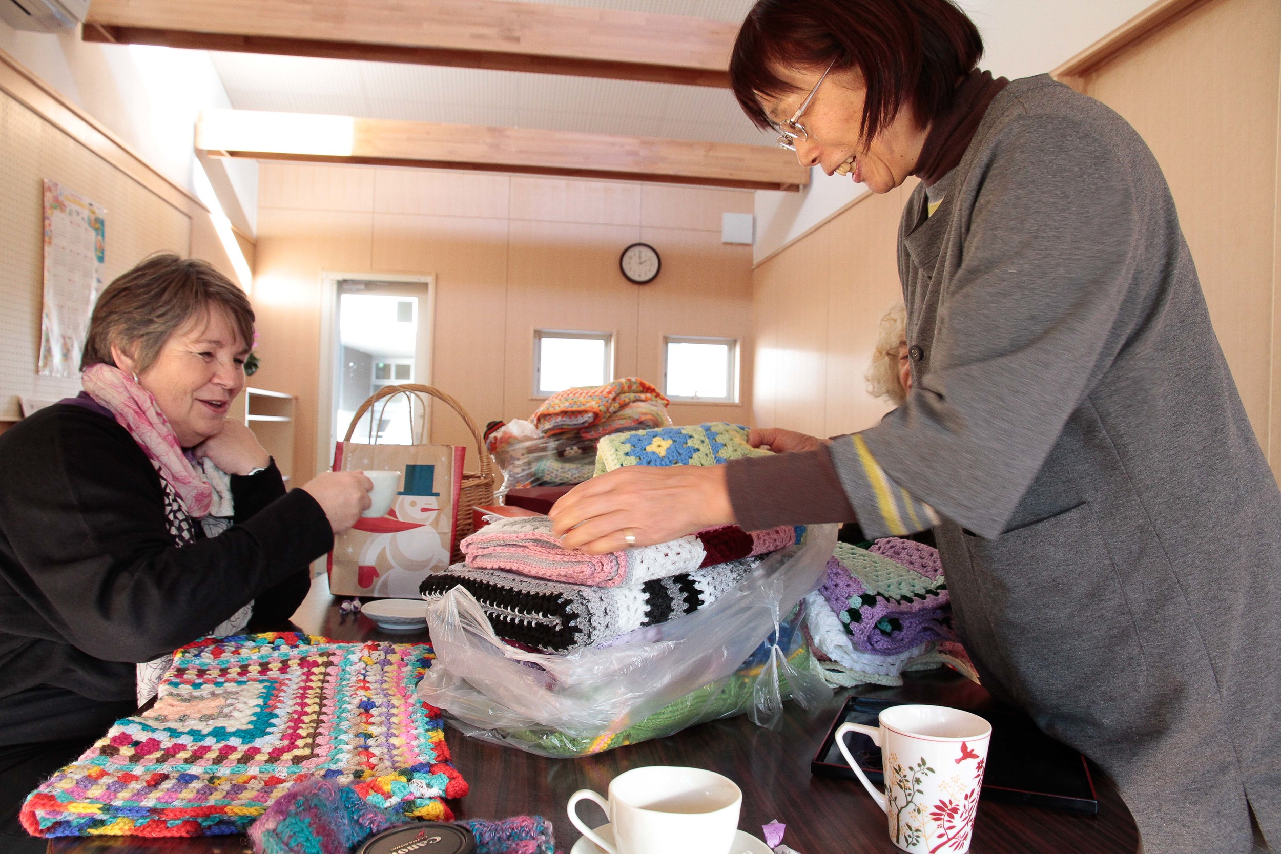 Mrs Utsumi, founder of the Mother's Home, looking at all the beautiful blankets.
