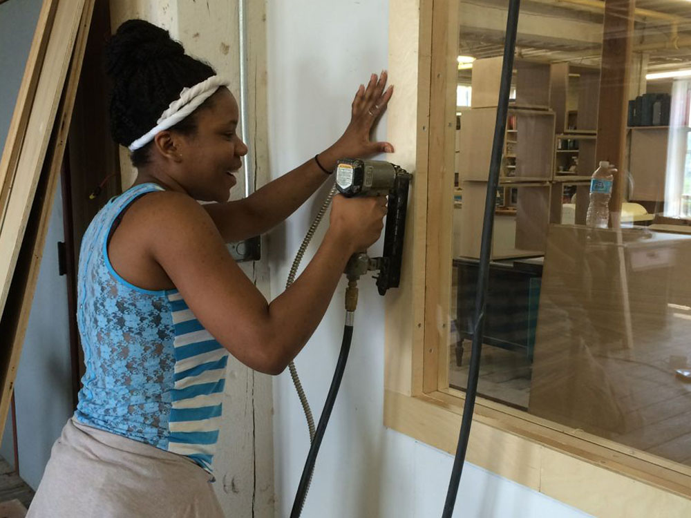 Elizabeth Felix installs the wood trim around their classroom window