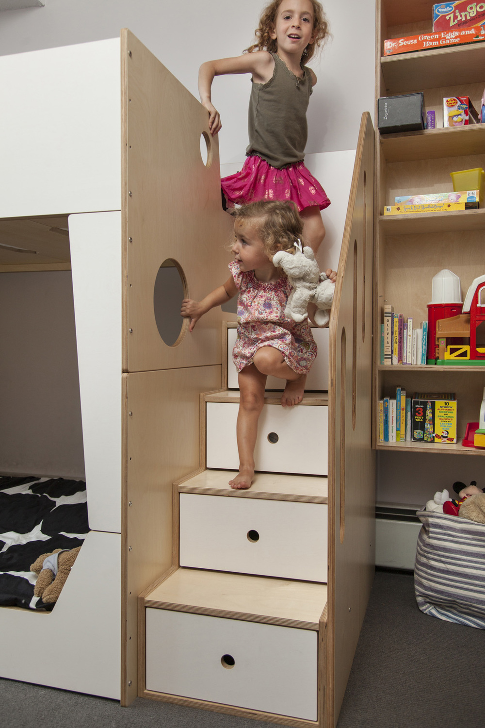 In these straight stairs, storage drawers are placed directly below the treads. Strategically-placed circular cut-outs become grips for the kids.