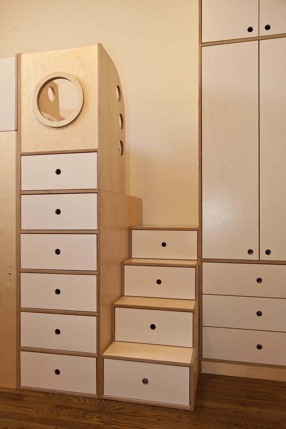 U-shaped stairs with 10 storage drawers and a porthole above to peer from