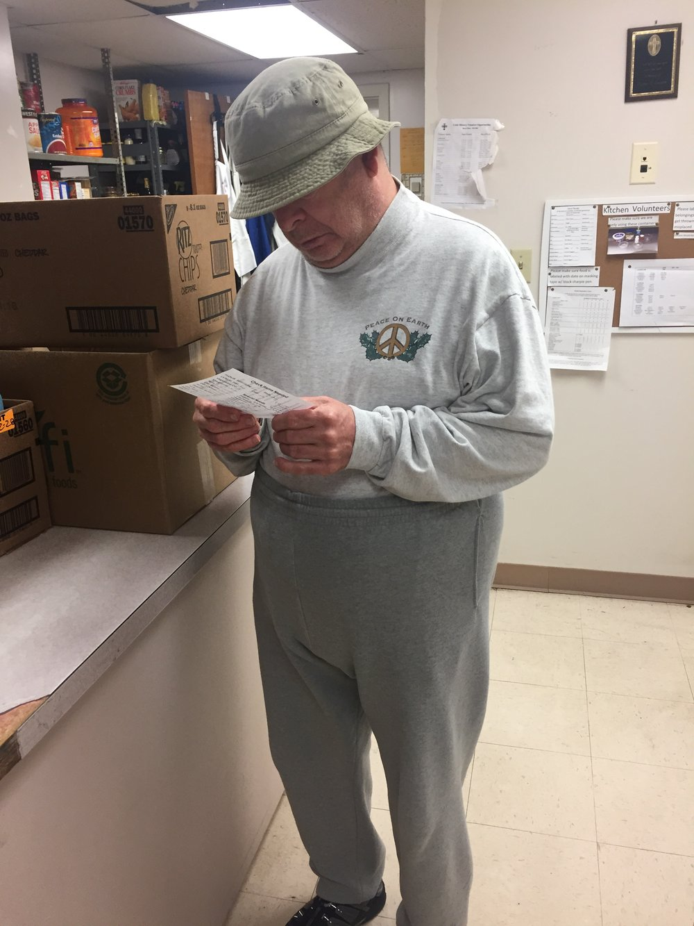 Volunteer Tim O'Connor looks over a list of foods requested by a client at the Downtown Crisis Ministry. Tim enjoys packing food boxes and bags for the clients, because he was one himself several years ago.