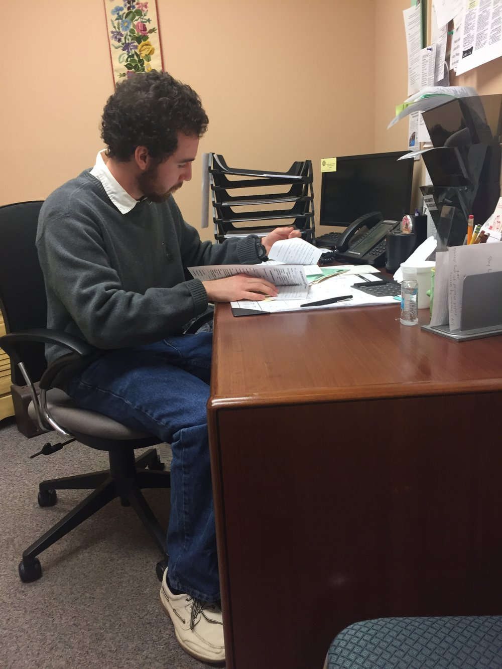 UNC Asheville senior David Johnson, who volunteers as a counselor in the Crisis Ministry, goes through a client's paperwork before a meeting. Johnson sees how grateful clients are when they're able to get assistance with food.