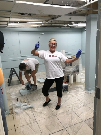 A BB&T Lighthouse volunteer takes a break while painting the educational playroom at Steadfast House. The blue paint color was chosen specifically according to principles of trauma-informed care.