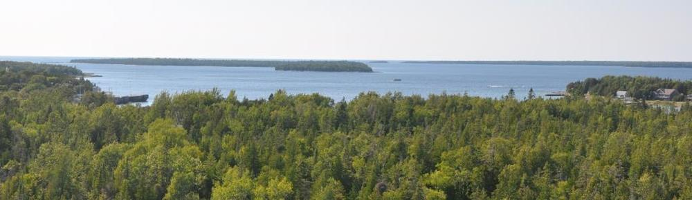 A view over Fathom Five park, with the harbour of Tobermory to the left, the open water of Lake Huron beyond and Georgian Bay to the right. The wreck of the Alice G lies in the centre foreground.