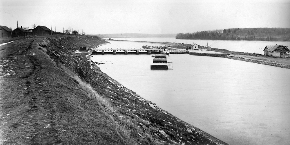 A photograph of Lock 21 looking east, thought to have been taken about 1904. The buildings to the left are on the site of the present information pavilion, with the water level today being about a metre higher than the top of the embankment. Our dive in the video took us down the slope to the railing at the top of the weir, then over the railing to the bottom of the canal, through the sluice gates (underwater in this photo)  and out the other side (photographer unknown).