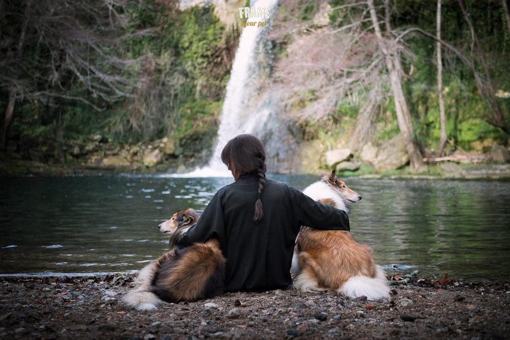 Set and Vincent laying with their mom in front of a waterfall.