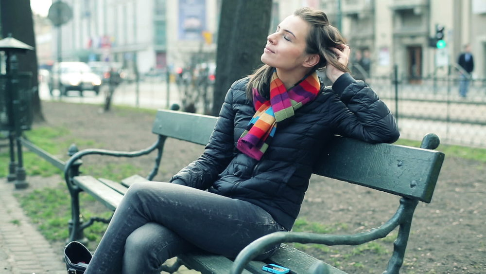 stock-footage-happy-beautiful-woman-relaxing-on-bench-in-city-park.jpg