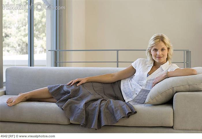 woman_relaxing_with_feet_up_on_sofa_at_home_smiling_side_view_portrait_4542.jpg