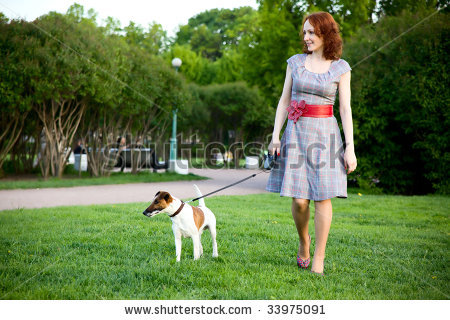 stock-photo-young-woman-walking-with-her-dog-in-a-park-33975091.jpg