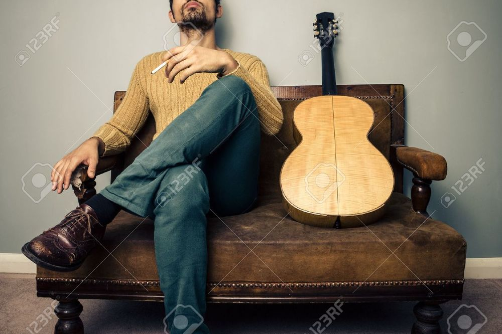 21994729-Stereotypical-musician-with-his-guitar-is-sitting-on-a-sofa-and-smoking-a-cigarette-Stock-Photo.jpg