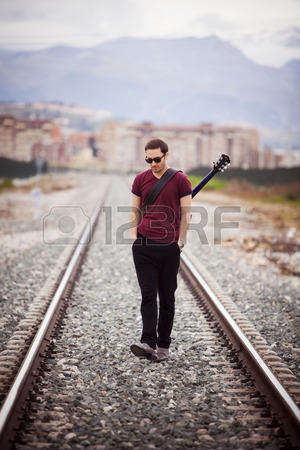 27084199-young-male-musician-walking-with-his-acustic-guitar.jpg