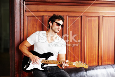 stock-photo-14949270-male-model-in-sunglasses-playing-a-guitar-against-wooden-panel.jpg